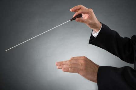 バトンを保持している男性オーケストラ指揮者の手のクローズ アップ