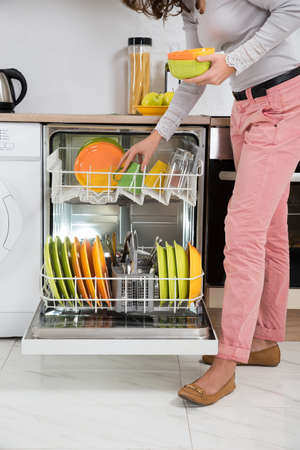 dishwasher: Woman Standing In Kitchen Removing Bowls From Dishwasher