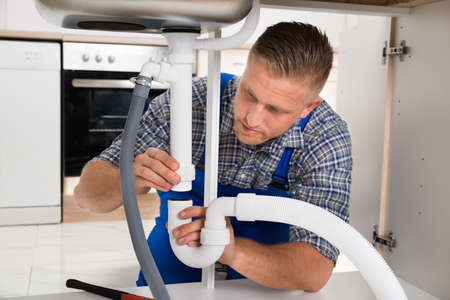 plumbing tools: Young Plumber Repairing Pipe Of Sink In Kitchen Stock Photo