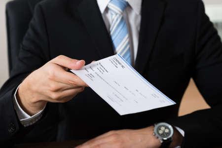 chequera: Primer plano de las manos hombre de negocios dando Cheque En Office