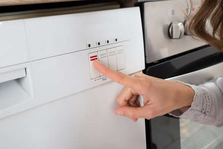 activating: Close-up Of Person Hands Pressing Button Of Dishwasher