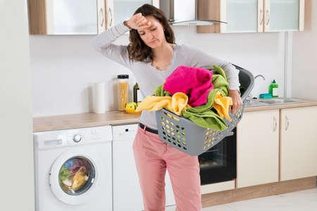 lavando ropa: Mujer Cansada joven que lleva Cesta Con Ropa En Cocina Habitación