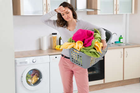exhausted: Young Tired Woman Carrying Basket With Clothes In Kitchen Room