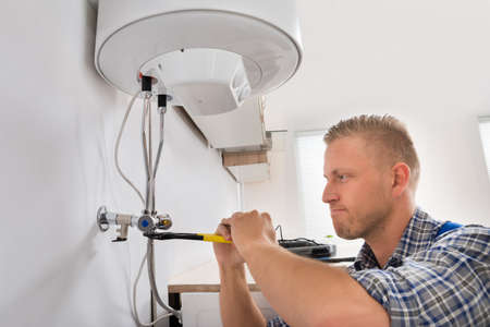 hydraulic: Male Repairman Repairing Electric Boiler With Wrench At Home