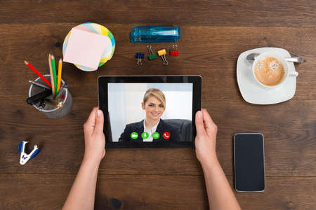 Person Videochatting With Businesswoman On Digital Tablet