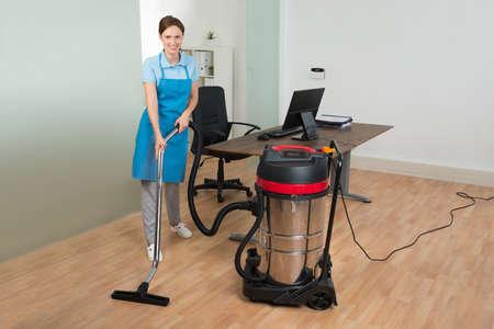Felice femminile dell'operaio di pulizia del pavimento Con L'aspirapolvere In Ufficio Archivio Fotografico - 43693587
