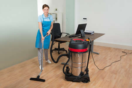 office uniform: Happy Female Worker Cleaning Floor With Vacuum Cleaner In Office