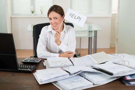 business help: Young Businesswoman With Invoices Asking For Help At Desk Stock Photo