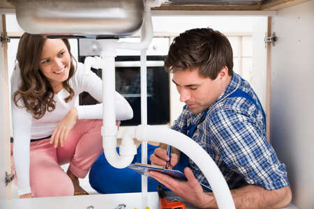 Happy Woman Looking At Plumber Writing On Clipboard View From Under The Sink Stockfoto