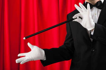 mago: Primer Del Mago en traje mostrando truco con la varita mágica Foto de archivo