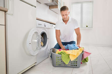 man kneeling: Young Man Kneeling On Floor And Putting Colorful Towels Into The Washing Machine