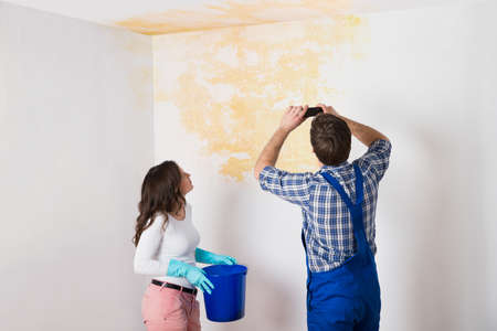 Handyman With Woman Photographing Water Damaged Ceiling With Mobile Phone At Home Stock Photo