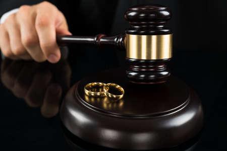 casamento: Close-up das mãos do juiz Bater Gavel Com Anéis Dourados Na Mesa