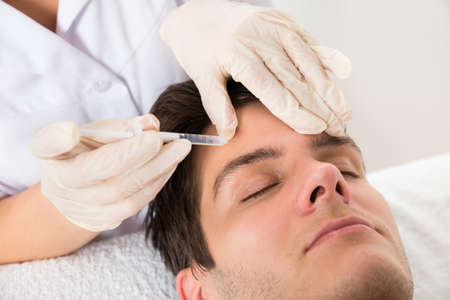 inyeccion: Hombre joven que se Botox Tratamiento En la Cl�nica de Belleza Foto de archivo