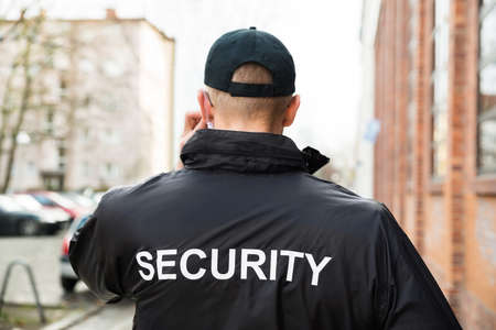 Close-up Of Male Security Guard Wearing Black Jacket Stock Photo