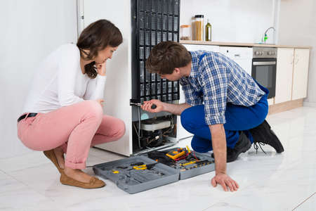 fridge: Young Repairman Repairing Refrigerator In Front Of Beautiful Woman Stock Photo