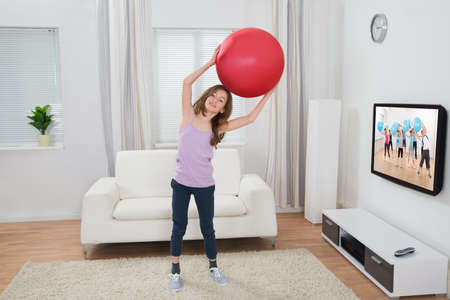 Happy Girl Holding Fitness Ball In Front Of Television At Home photo
