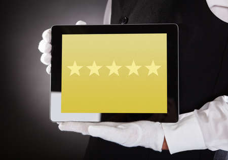 hotel reviews: Close-up Of Waiter Showing Rating System On Digital Tablet