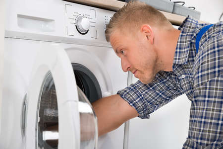 Close-up Of Professional Handyman In Overall Repairing Washing Machine Archivio Fotografico