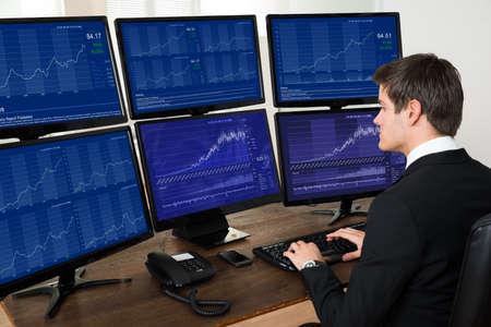 comercio: El hombre de negocios joven que trabaja con gráficos en seis computadoras en Escritorio