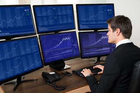 person computer: Young Businessman Working With Graphs On Six Computers At Desk