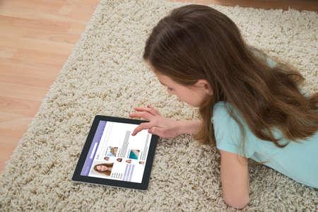 kinderen: Meisje met behulp van social networking site op digitale tablet thuis