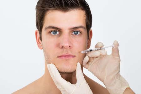 若い男の顔に注射器を注入する人の手のクローズ アップ