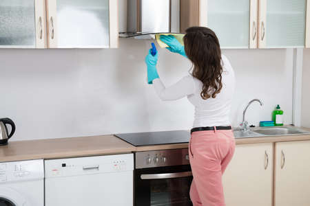 stove: Woman Cleaning Cooker Hood With Rag In Kitchen At Home Stock Photo