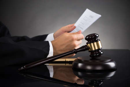 courtroom: Close-up Of Judge Holding Document With Gavel At Desk Stock Photo