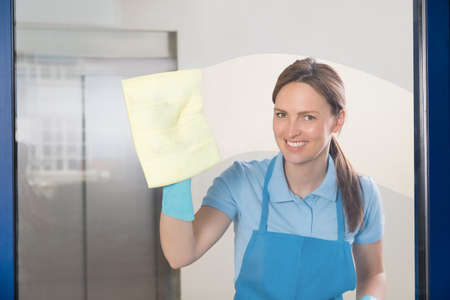 cleaning service: Young Happy Female Janitor Cleaning Glass With Rag
