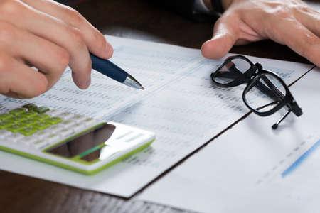 papeles oficina: Primer De La Persona Mano Cálculo de Finanzas con los vidrios en el escritorio Foto de archivo