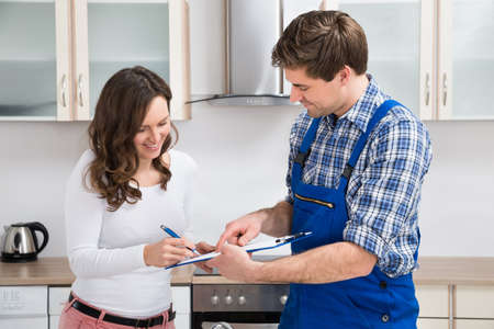 firmando: Feliz portapapeles de escritura de la mujer encendido con Hombre fontanero permanente en sala de cocina Foto de archivo