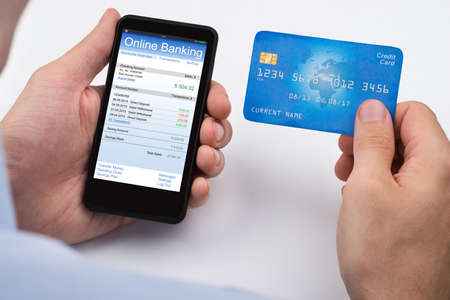 Close-up Of Person With Credit Card And Mobile Phone Doing Online Banking Zdjęcie Seryjne