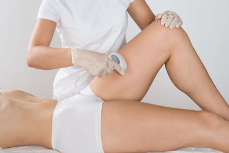 hair treatment: Close-up Of Young Woman Having Laser Treatment On Thigh At Beauty Clinic