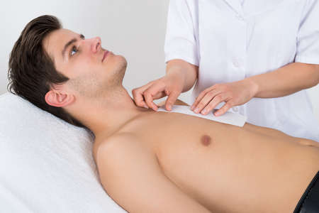 depilate: Close-up Of Beauty Therapist Waxing Young Mans Chest Lying On Bed Stock Photo
