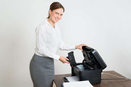 copier: Young Happy Businesswoman Holding Laser Cartridge With Printer At Desk