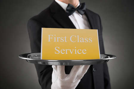servings: Close-up Of Waiter Wearing Glove Giving Plate With The Text First Class Service On Board