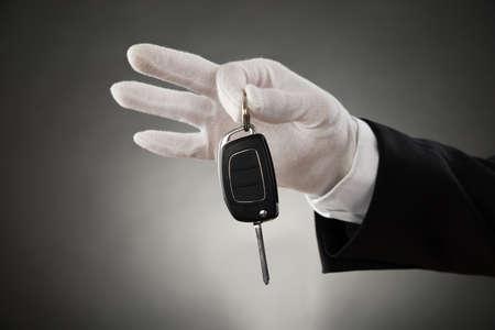guantes: Primer plano de Garzón Manos en White Glove Holding llave del coche Foto de archivo