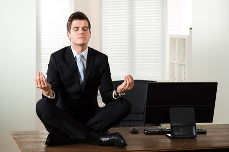 workplaces: Young Businessman Doing Meditation At Desk In Office