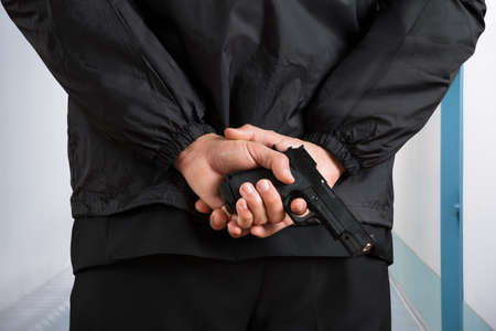 bodyguard: Close-up Photo Of Bodyguard Hands Holding Pistol Stock Photo