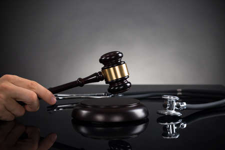 conclusive: Close-up Of Hands With Gavel And Stethoscope At Desk In Courtroom