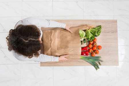 view woman: High Angle View Of Young Woman Removing Vegetables From Shopping Bag Stock Photo