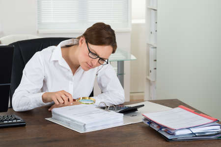 Young Businesswoman Checking Invoice With Magnifying Glass At Desk