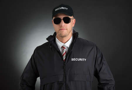security uniform: Portrait Of Young Bodyguard In Uniform Wearing Sunglasses Over Black Background Stock Photo