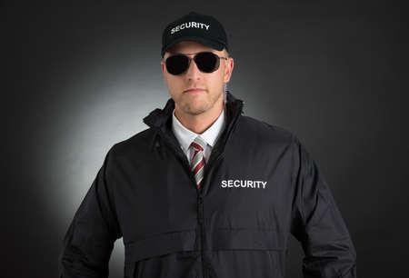 Portrait Of Young Bodyguard In Uniform Wearing Sunglasses Over Black Background Archivio Fotografico