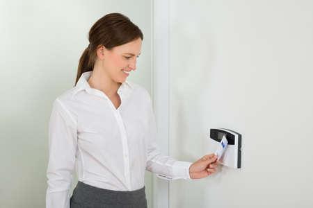 sistema: Empresaria joven que sonr�e mientras Inserci�n Keycard En el sistema de seguridad de la puerta Foto de archivo