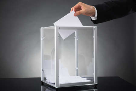 vorschlag: Close-up Von Businessperson Hands Putting Stimmzettel In Box Am Schreibtisch
