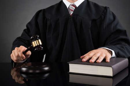 小槌と本をデスクで男性裁判官のクローズ アップ
