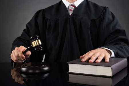 courtroom: Close-up Of Male Judge With Gavel And Book At Desk Stock Photo