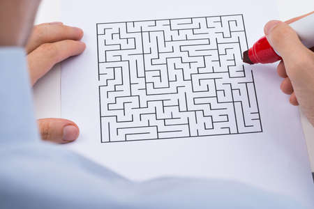 solved maze puzzle: Close-up Of Person Hand With Maze On Paper And Red Marker Stock Photo
